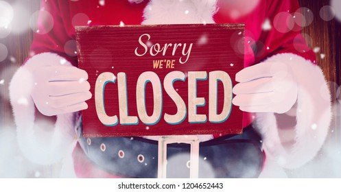 Digital composite of Sorry we're closed sign in hands of Santa with snow