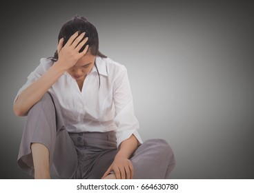 Digital composite of Stressed business woman sitting down against grey background
