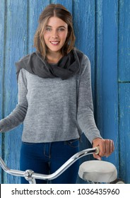 Digital composite of Woman against wood with bicycle and scarf