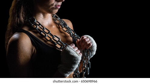 Digital composite of Woman with chains against black background