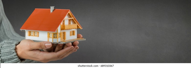 Digital composite of Woman holding a house against grey background as concept of insurance