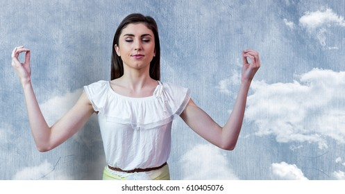 Digital composite of Woman Meditating peaceful by cloud wall