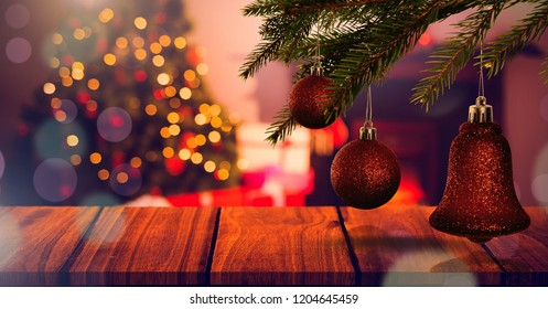 Digital composite of Wood surface and Christmas tree at home with hanging decorations