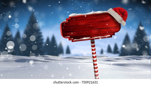 Digital composite of Wooden signpost in Christmas Winter landscape and Santa hat