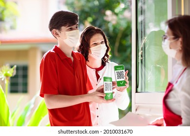 Digital covid-19 vaccination certificate on mobile phone. Coronavirus vaccinated people scan QR code on restaurant entrance. Negative test, completed vaccine and immunity proof for safe travel. - Shutterstock ID 2010031670