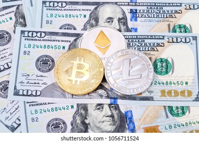 Digital cryptocurrency Bitcoin, Ethereum and Litecoin lying on the one hundred american dollar bills. Business concept of new virtual money