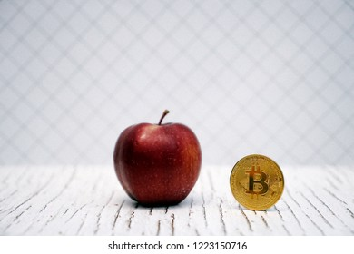 Digital currency physical gold bitcoin coin near apple. Selective focus with copy space for text.