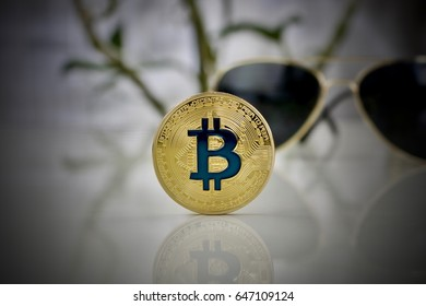 Digital currency physical gold bitcoin coin and gold sunglasses