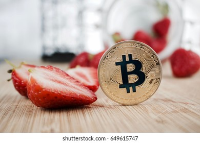 Digital currency physical gold bitcoin coin near fresh strawberries