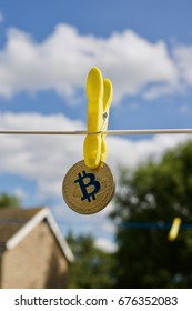Digital currency physical gold bitcoin coin on white line. Yellow clips.