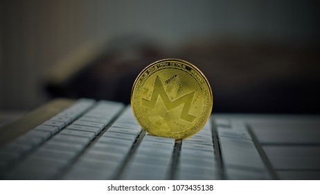 Digital currency physical metal monero coin on the white computer keyboard.