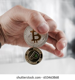 Digital currency physical silver bitcoin and gold peercoin in hand.
