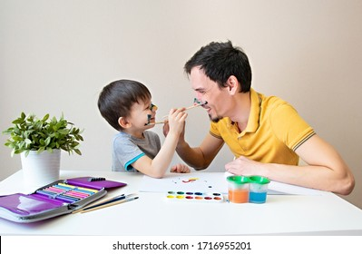 Digital detox. Father and child spend a fun time while drawing. Happy family. Father and son paint each other's faces. Spending more time with loved ones. Father playing with son, they are painting