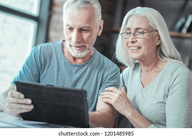 Digital device. Pleasant smart beaded man sitting together with his wife and holding a tablet while working on it