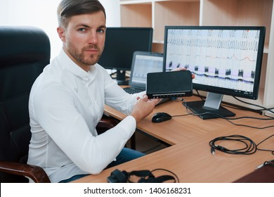 Digital device. Polygraph examiner works in the office with his lie detector's equipment.