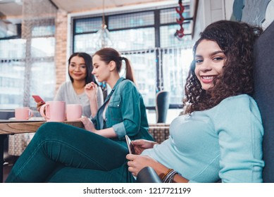 Digital device. Positive happy woman holding her new smartphone while sitting together with friends