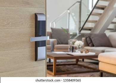 Digital Door handle or Electronics knob  for access to room security, Door wooden half opening through interior living room background, selective focus