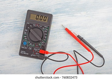 Digital electric tester multimeter on wooden background.