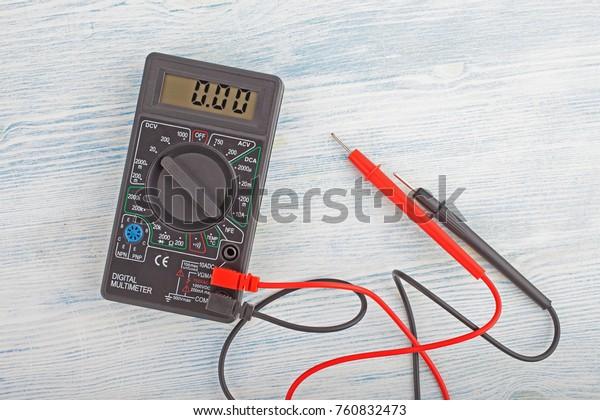Digital electric tester multimeter on wooden background.