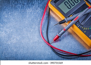 Digital electric tester on metallic background electricity concept.