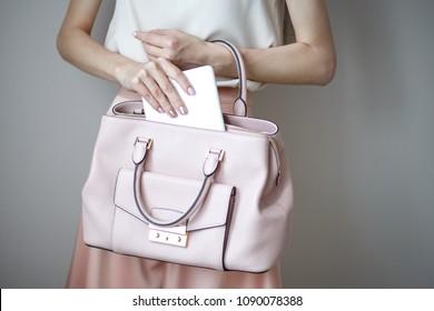 Digital electronic tablet on a woman's hands. Leather light pink handbag, summer elegant style