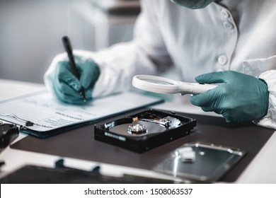 Digital Forensic Science. Police Forensic Analyst Examining Computer Hard Drive.