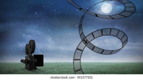 Digital generated image of film reel against video camera and night sky in background