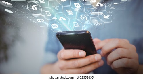 Digital interface with digital icons over mid section of man using smartphone. global networking and business technology concept
