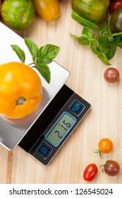 Digital kitchen scale on table surrounded with fresh tomatoes, and basil.