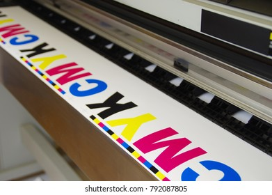Digital large inkjet machine. Plotter printed CMYK test on white paper.