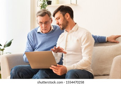 Digital Literacy. Middle-Aged Son Teaching Elderly Father To Use Laptop Computer, Social Media And Internet Sitting On Couch Indoor