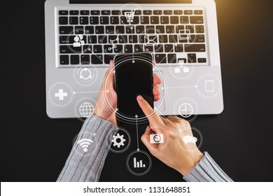 Digital marketing media in virtual screen.businessman hand working with mobile phone and modern computer and business strategy with VR icon diagram at office in morning light as concept