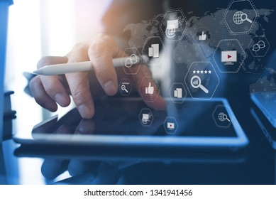 Digital marketing media (website ad, email, social network, SEO, video, mobile app), business strategy analysis concept with modern web icons. Man working on digital tablet in modern office