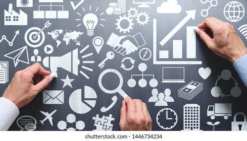 Digital marketing meeting. Businessmen drawing many icons on chalkboard.