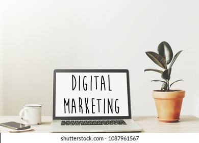 digital marketing text on laptop screen on wooden desktop with phone, notebook, coffee and plant. business workspace. business analysis and strategy