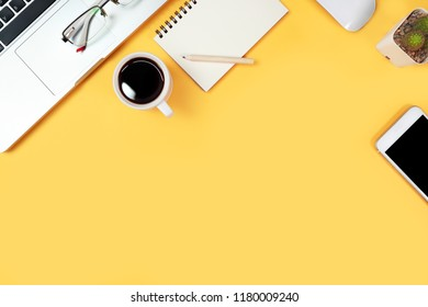 digital marketing work desk with laptop computer, office supplies, coffee cup and cell smartphone on yellow pastel background