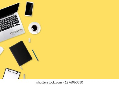 digital marketing work desk with laptop computer, office supplies, coffee cup and cell phone on yellow pastel background