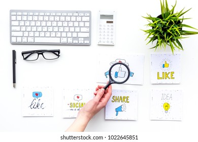 Digital marketing. Work desk of marketing specialist with social media icons and symbols. Hand with magnifiger on white background top view copy space