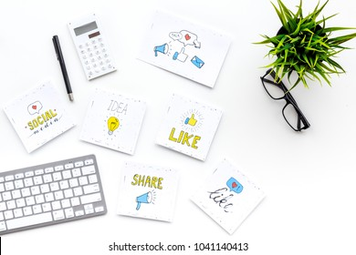 Digital marketing. Work desk of marketing specialist with social media icons and symbols on white background top view copy space