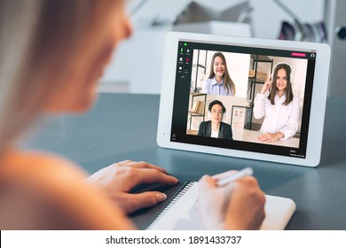 Digital meeting. Corporate videocall. Web chat. Distance work. Pandemic WFH. Diverse multiracial team in headphones discussing project on tablet screen female employee taking notes at home office.