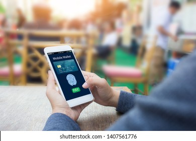 Digital mobile banking wallet concept.Hands holding mobile phone on blurred frestaurant as background