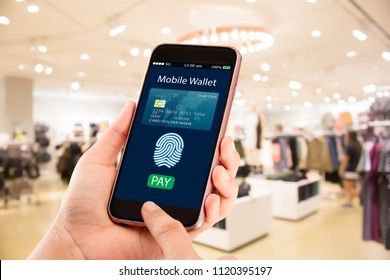 Digital mobile wallet concept.Hands holding mobile phone on blurred fashion store as background