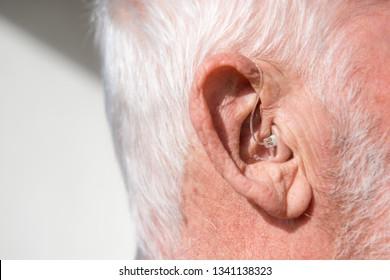 Digital modern hearing aid in the ear of senior man