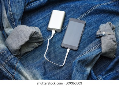 Digital modern stil life. Charge smart phone from power bank. Mobile on jeans jacket texture.