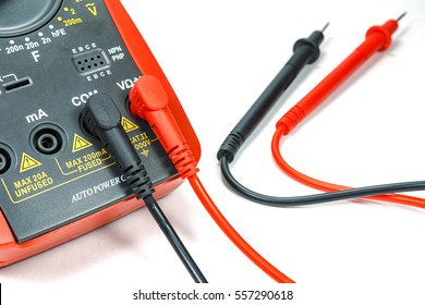 Digital multimeter with attached probes on a white background