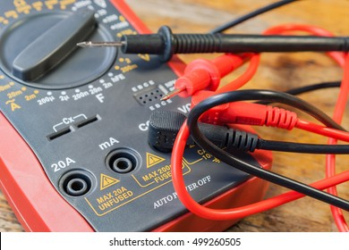 Digital multimeter with the connected probes on a table in a workshop