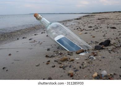 Digital native castaway sending a help message in a bottle.