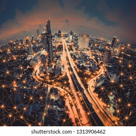 Digital network connection lines of Sathorn road, Bangkok Downtown, Thailand. Financial district and business centers in smart urban city in Asia. Skyscraper and high-rise buildings at night.