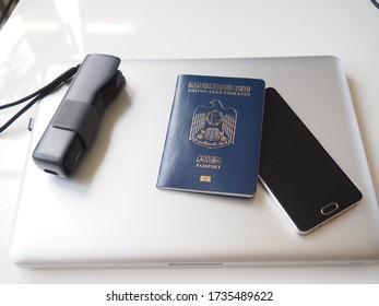 Digital Nomad travel gear of an Arabian Emirati Worker like Camera, Mobile Phone, Laptop and Passport