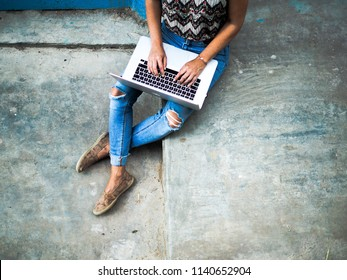 digital nomad woman in hipster jeans tap on her laptop while sitting on grey stairs outside in the streets of morocco